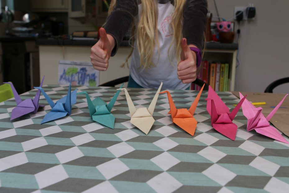 7 origami cranes in rainbow colours and a young girl with her thumbs up