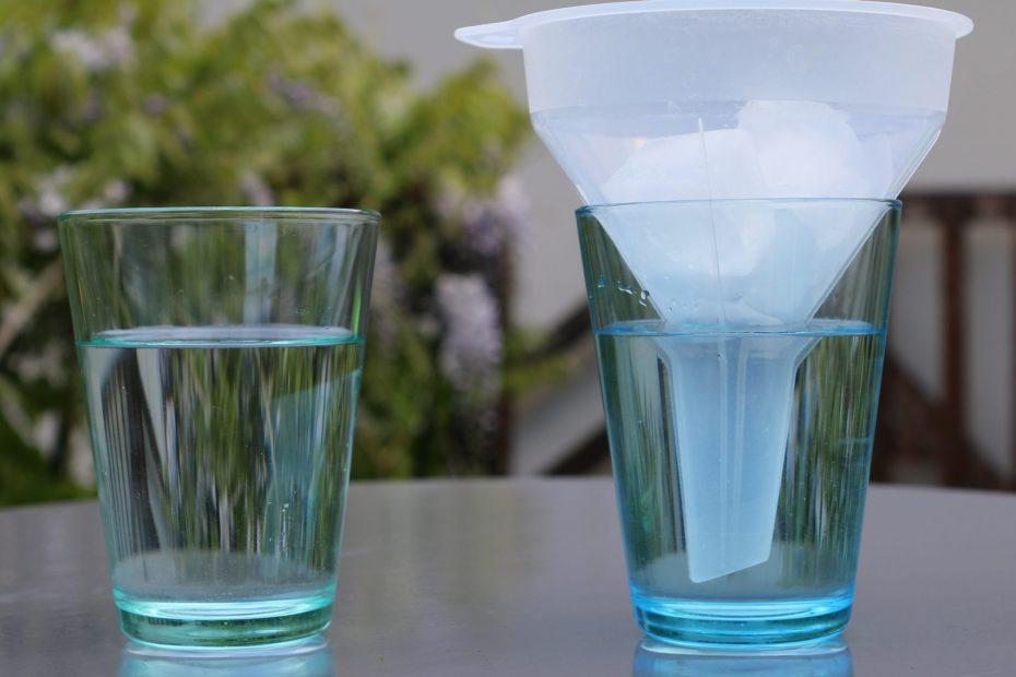 two cups, ones with a funnel filled with ice.