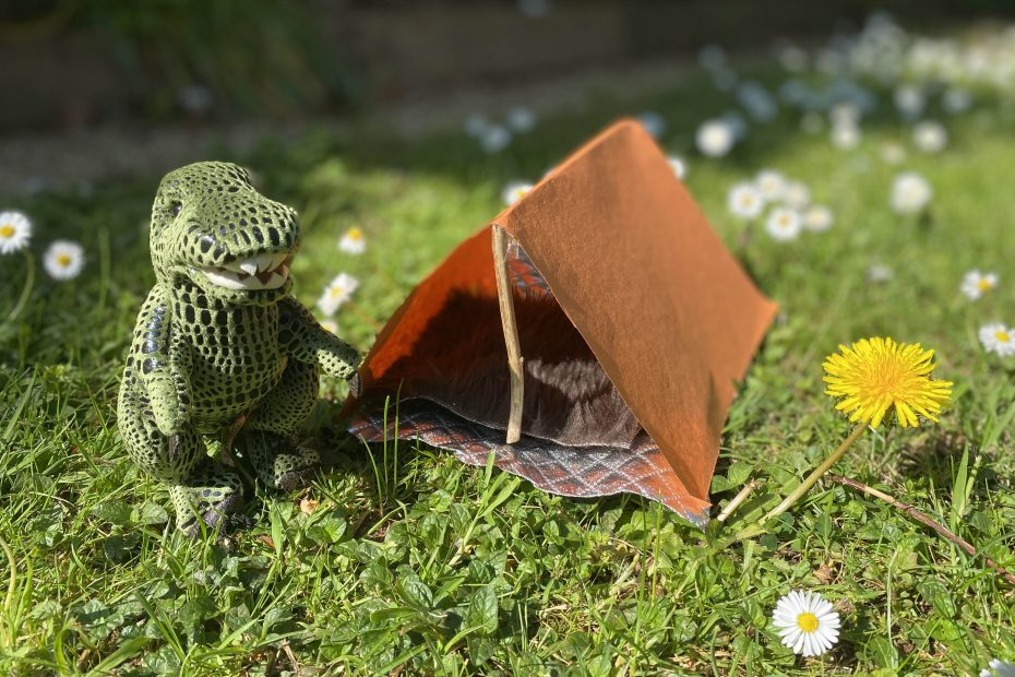 miniature campsite in the grass with toy dinosaur