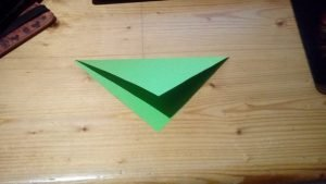 green paper folded from top corner to bottom corner