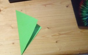 green paper folded from left corner to right corner