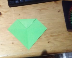 Green paper folded top corner to centre fold