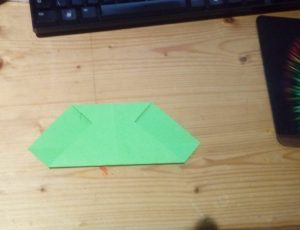 green paper folded bottom corner to top edge